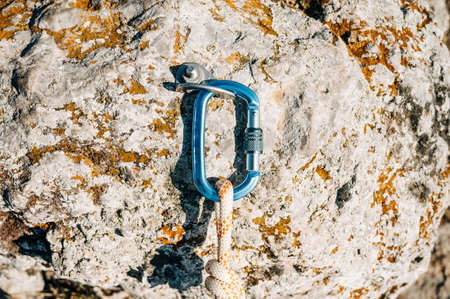 Close Up of climbing gear, Anchor, Rope, and Carabiner with cliff rock as a backdrop.