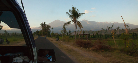 gradually: View over mount rinjani from the Car during the way to the Start point in the early morning. Stock Photo