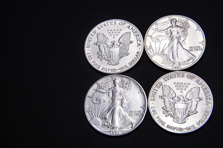 American silver dollars  from both sides on the black background Stock Photo
