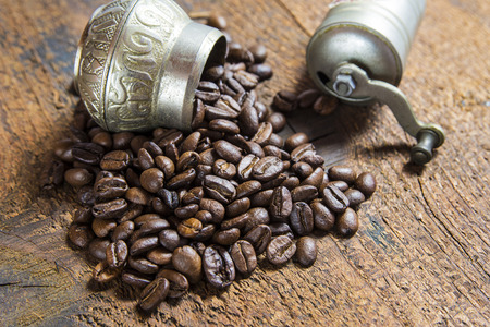 Roasted coffee beans spilled over the wood background