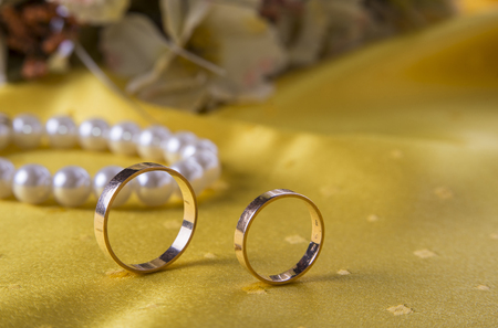 jewerly: Closeup of wedding rings on the yellow tablecloth background with and jewerly