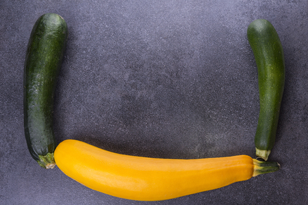 Three zucchini on the kitchen table, two green, one yellow