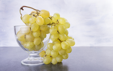 Yellow friut grapes is inside and outside of the glass