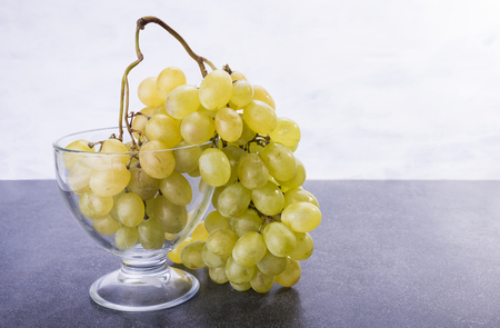 Sweet friut grapes in the glass and on the table Stock Photo