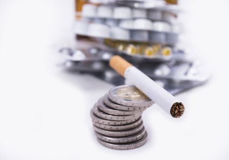 Cigarette on the euro coins. Smoking costs money and is harmful