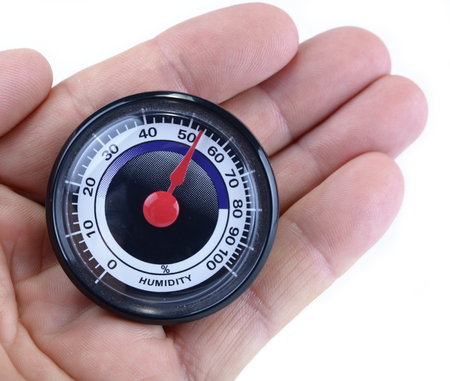 Analog humidity meter in the hand on white