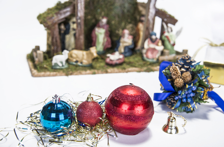 creche: Christmas background with decorations  bells, ribbon and balls on white.