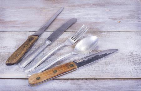 Old aluminium fork knife spoon on white wood