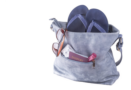 Travel concept. Woman bag with beach slippers, sunglasses, passport, condoms, lipstick. Stock Photo