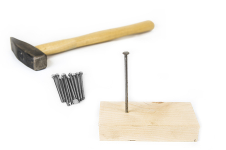 Hammer with nails and wood on white background.