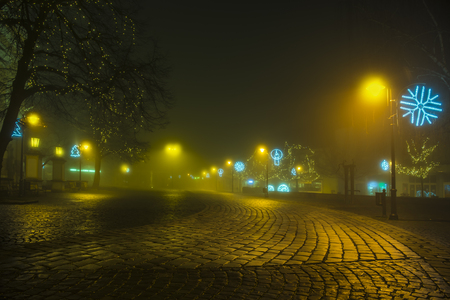 Town in the night in fog with christmas decoration Stock Photo