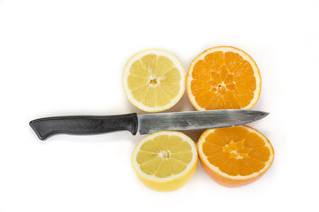 Cut orange and lemon on two  halves with kitchen knife on the white Stock Photo