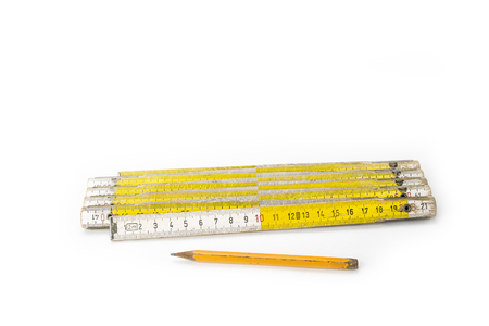 Old yellow construction folding meter on the white background