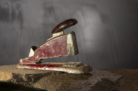 Old stapler on the stone and dark background