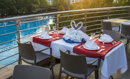 Table with chairs served for couple on the pool background. Romantic event outdoor.  Summer vacation concept