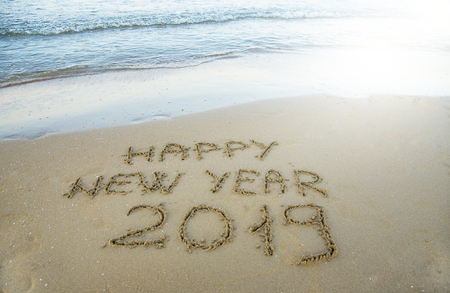 Happy new year written on the sand