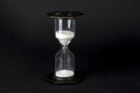 Hourglass on a black background. Time is money concept 免版税图像