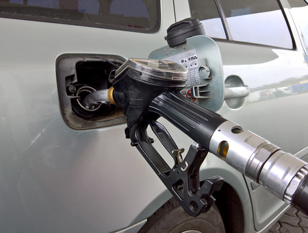 Car at a gas station. Gasoline pistol pump inserted in a tank