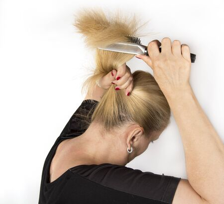 Mature female is combing her hair