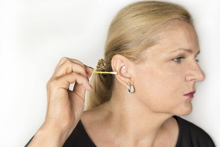 Woman cleaning her ear with a swab