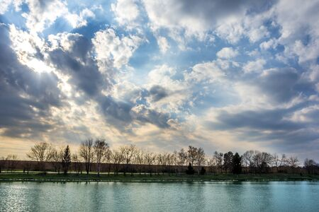 Lake as water reservoir with trees and sky in the spring