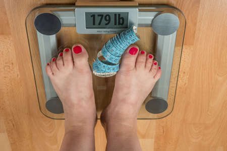 A woman stands with two feet on a scale. Overweight concept