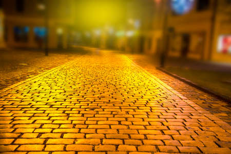 Wet cobblestone road in the night with light reflections Stock Photo