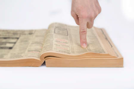 Finger pointing out in a phonebook on a white Zdjęcie Seryjne