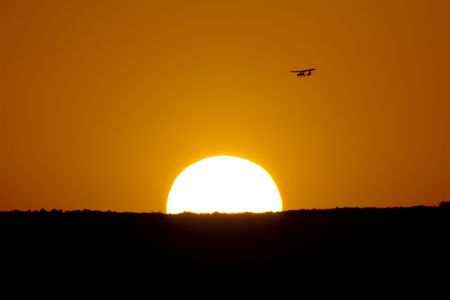 Sunset with airplane, image to the telescope of the sun and airplane