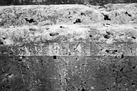 This is a Old greek writing in the ruins of the Syracuse greek theater Stock Photo