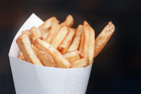 Franse frietjes in papieren bundel. Donkere achtergrond. Plaats voor tekst en copyspace Stockfoto