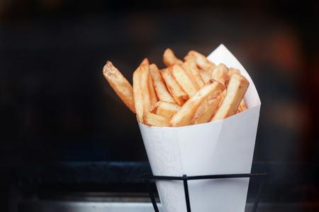 Franse frietjes in papieren bundel. Donkere achtergrond. Plaats voor tekst en copyspace