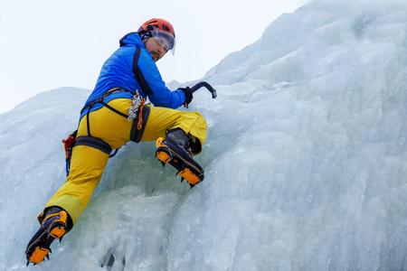 Rock climber climbs a frozen waterfall.
