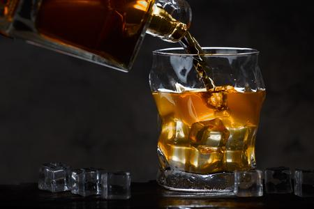 Bottiglia di whisky che scorre in un bicchiere di ghiaccio su uno sfondo scuro