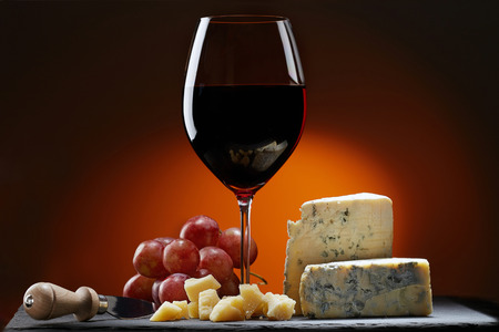 Glass of wine with grapes and a piece of cheese with mold, Parmesan cheese and cheese knife.  Orange background. 写真素材