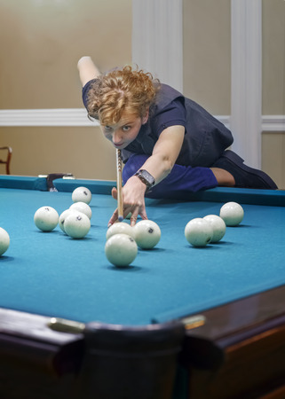 Curly-haired girl plays Billiards, performs a difficult blow. Curly-haired girl plays Billiards, performs a difficult blow. The concept of a professional player. Russian billiards Фото со стока