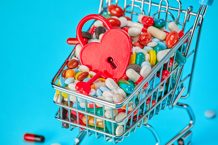 Basket of pills and red heart-shaped padlock. Blue background. Concept: a Healthy heart. Pharmaceuticals and medicine prolong life. Copy space for text