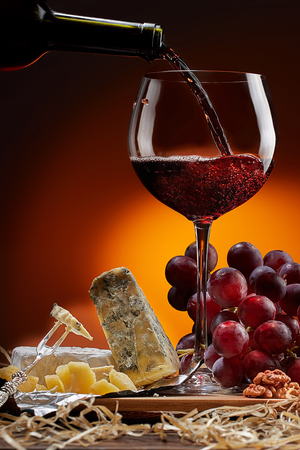 Wine flows from the bottle into the glass. On the table are different varieties of cheese and grapes. Dark background. 写真素材