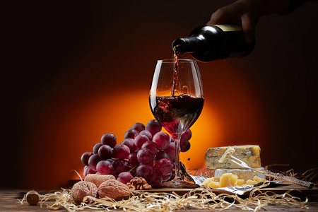 Wine flows from the bottle into the glass. On the table are different varieties of cheese and grapes. Dark background. Stock Photo