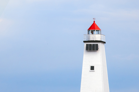 White lighthouse with a red roof against the sky.