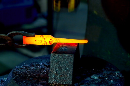 hotsteel on the anvil to hold the anvil blacksmith tongs