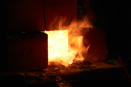 Flames burst from the forge