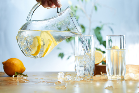 Water from a Decanter with sliced lemon, ice poured into a glass. Stock Photo
