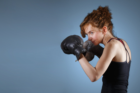 Boxer girl in a dark sports uniform stands in a rack. Concept: womens self-defense, martial arts, womens Boxing.