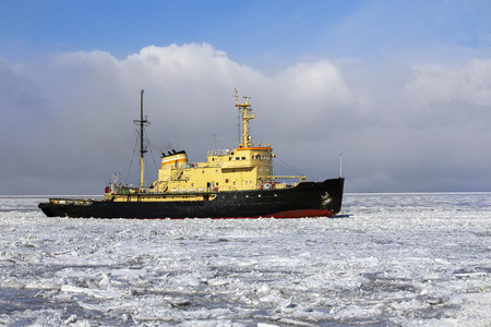 Icebreaker is moving in the ice on the background of sky with clouds Stockfoto