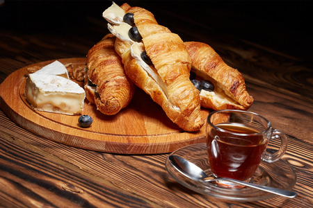Coffee with croissant, nuts, Camembert cheese on a dark wooden background.