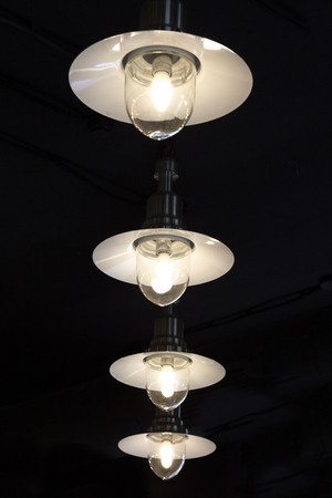 A lot of light Bulbs with shades on a dark background Stock Photo