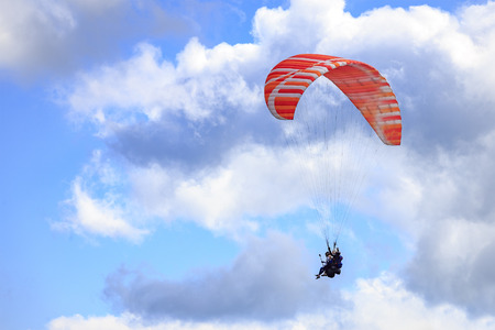 Paraglider with two people (tandem) flying against the blue sky with clouds.