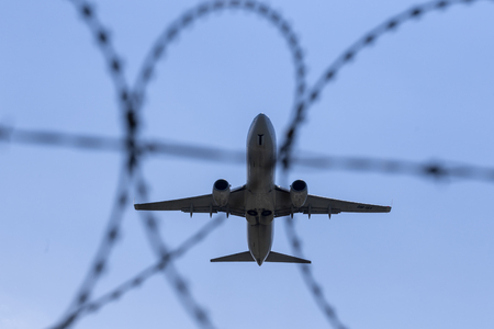 The plane flies on the background of barbed wire Stock Photo