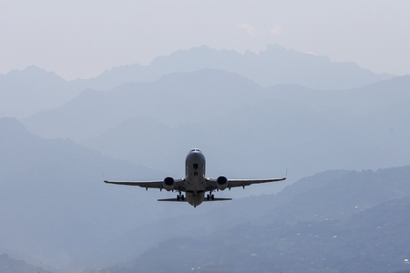 Aircraft, airliner with landing gear comes to land on the background of the mountains. Rear view.
